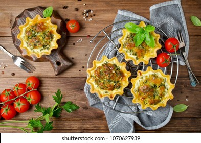 Baked homemade quiche pie in mini metal forms served with fresh greens on old plank wooden background