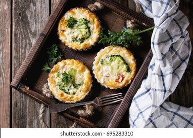 Baked homemade quiche pie in mini metal forms served with fresh greens, kitchen towel and fork in dark wood tray on old plank wooden background. Flat lay with space