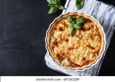 Baked homemade quiche pie in white ceramic form served with fresh greens on white serving board on black wooden burned background. Flat lay with copy space