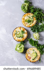Baked homemade vegetable broccoli quiche pie in mini metal forms served with fresh greens on gray concrete background. Flat lay with copy space. Ready for eat