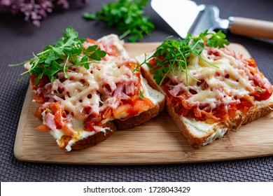 Baked hot sandwiches on white bread with fried vegetables in tomato sauce, Servelat straws, melted cheese and green watercress on a wooden Board