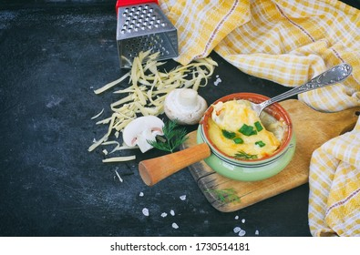 juliana al horno con paladines, cebollas y queso sobre mesa negra, sobre tablero de madera, rallador, toalla a cuadros, vista superior