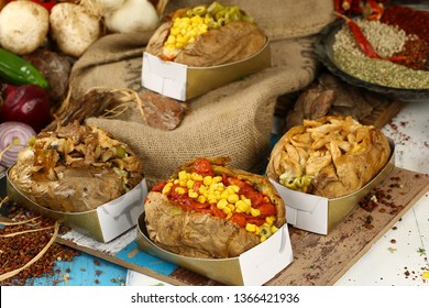 Baked kumpir potato stuffed with the cheese, sausage, olives, peppers and corn