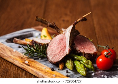 Baked lamb loin, served with asparagus. Dark background.