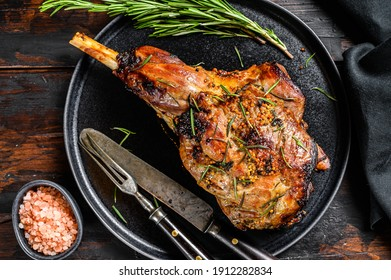 Baked lamb, sheep leg with rosemary. Dark wooden background. Top view