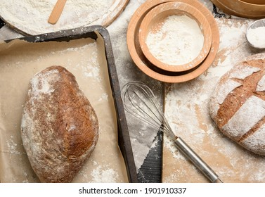 baked loaf of bread on the table and ingredients, kitchen utensils lie nearby, top view