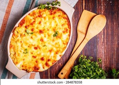 Baked macaroni and cheese with fresh oregano leaves in  rustic style.