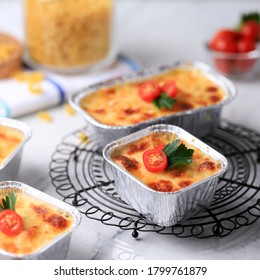 Baked Macaroni Schotel (Macaroni and Cheese) on Square Disposable Alumunium Foil. Garnish with Cherry Tomato