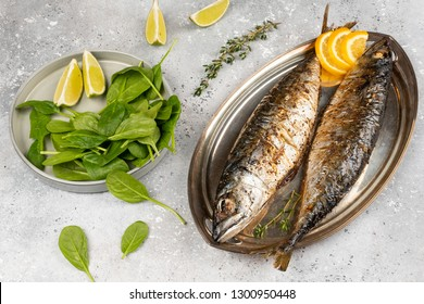 Baked mackerel fish on gray concrete background, top view