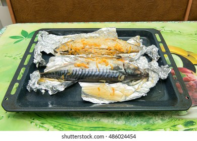 Baked mackerel in foil with vegetable oil and spices. Top view. Recipe home fish with vegetables in foil.