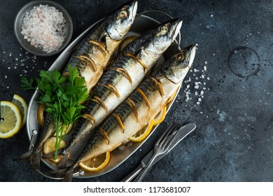 baked mackerel with lemon and herbs, dark background, top view