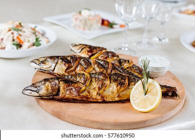 Baked mackerel with lemon on a white plate