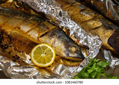 Baked Mackerel with salt, lemon and spices on foil. Cooking fish with herbs. Top view