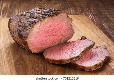 Baked meat on a wooden background. Roast beef.