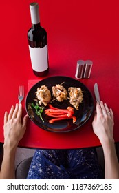 Baked meat with paprika and salad on a black plate and a bottle of wine on a red table. The girl is preparing for dinner. Top view