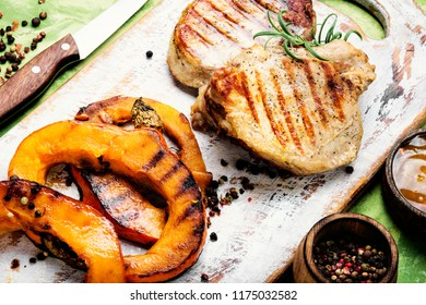 Baked meat with pumpkin on cutting board.Steak with pumpkin
