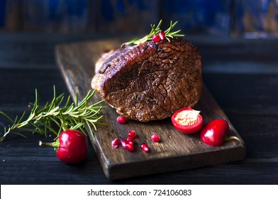 baked meat with rosemary and red pepper. steak. beef. dinner for men. dark photo. Black background. wooden board.