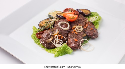 Baked meat with zucchini and eggplant on a white background