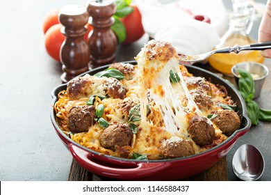 Baked meatballs with spaghetti, tomato sauce, basil and cheese with cheese pulled
