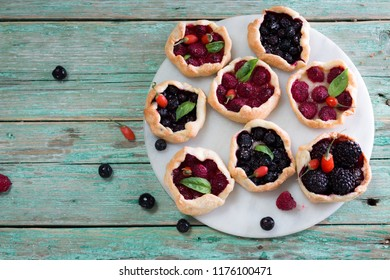Baked mini galette pie with berries on the table, homemade food