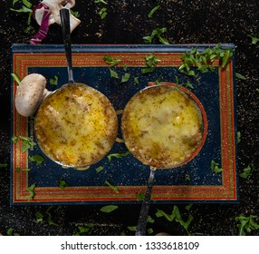Baked mushroom julienne with chicken and cheese in pots. Top view. Pot with a julienne.Julienne with mushrooms