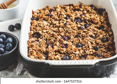 Baked oatmeal with blueberries and honey in the oven dish. Oatmeal fruit crumble pie.