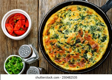 baked omelette with spinach, dill, parsley and green onions on a dark wood background. tinting. selective focus