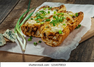 Baked open faced cheese sandwiches with mozzarella, gorgonzola and green onion on a rustic wooden table.