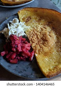 Baked pancake with apple and plum slaw lightly dusted with sugar