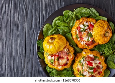 baked Patty Pan squash stuffed with rice, fried chicken meat, crispy fried bacon, bell pepper and served with green fresh spinach leaves and parsley on a black plate, view from above, close-up