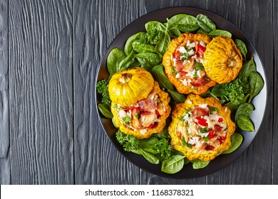 baked Patty Pan squash stuffed with rice, fried chicken meat, crispy fried bacon, bell pepper and served with green fresh spinach leaves and parsley on a black plate, view from above