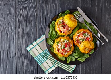 baked Pattypan squash stuffed with rice, fried chicken meat, crispy fried bacon, bell pepper and served with green fresh spinach leaves and parsley on a black plate