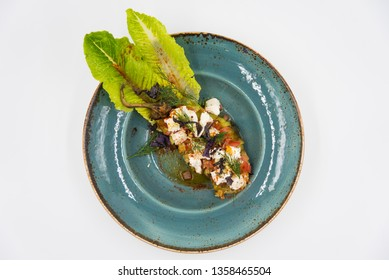Baked pepper with tomato, cheese and dill on the blue plate.