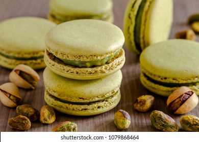 Baked pistachio flavored french macarons sitting on wooden table surrounded by fresh pistachio