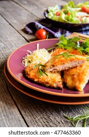 Baked pork cutlets coated in cheese and grated carrot, served with lettuce and tomato salad