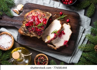 Baked pork meat with cranberry sauce. Christmas food. Winter meat recipe. Top view  on dark stone table.