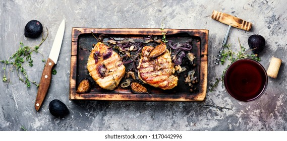 Baked pork meat in marinade with onion and figs.Steak with fruit sauce