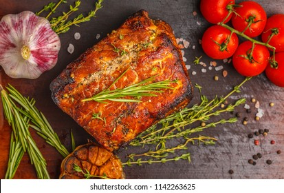 Baked pork with a thyme, rosemary, garlic on a wooden board, dark background, copy space.