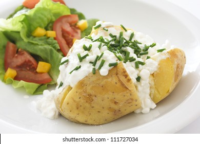 baked potato with cottage cheese, chives and fresh salad on a white plate