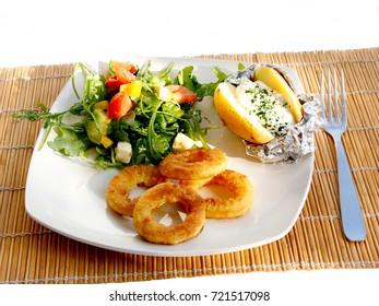 Baked potato with cream, salad and calamaris