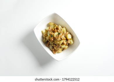 Baked potato with fried chanterelle mushrooms on a white plate