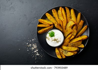 Baked potato with herbs and sauce in black ceramic dish on dark concrete or ceramic background. Selective focus. Top view. Place for text.