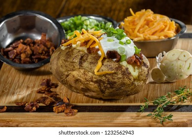 baked potato loaded with sour cream, bacon chives, and sharp cheese served on a cutting board
