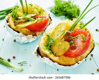 Baked potato with pickles, tomatoes and fresh greens. Shallow dof.