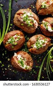 Baked potato, baked potatoes stuffed with butter, cream cheese and green onions, seasoned with freshly ground black pepper and sea salt flakes on a black background, top view