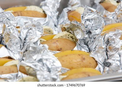 Baked potato, baked potatoes stuffed with butter, wrapped in tin foil ready to go onto the barbecue grill. High quality photo