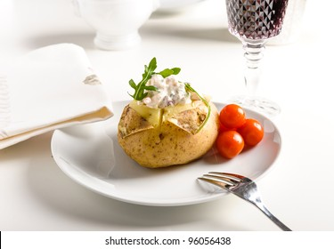 Baked potato with shrimps and some tomatoes