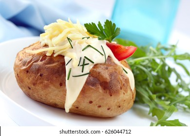 Baked potato with sour cream, grated cheese, chives, and salad.