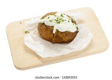 Baked potato with sour cream on wooden board on white background