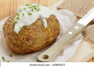 Baked potato with sour cream on wooden board
